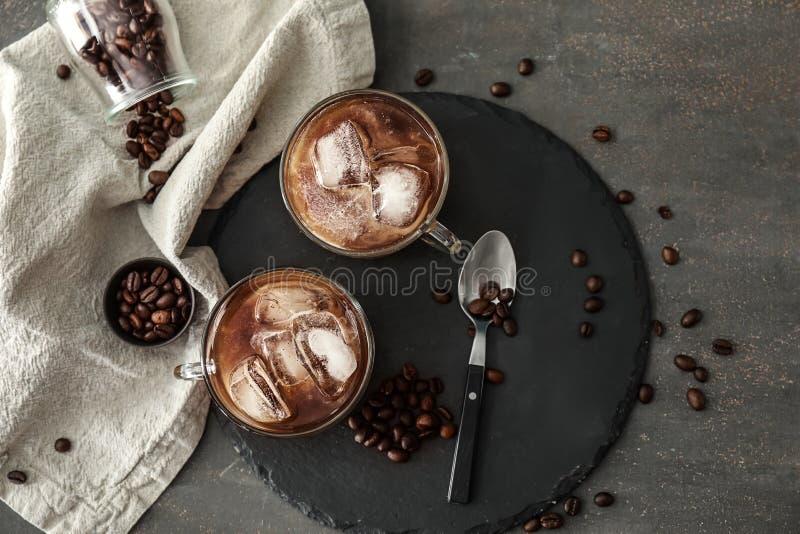 玻璃杯子用在板岩板材的冷的咖啡 库存图片