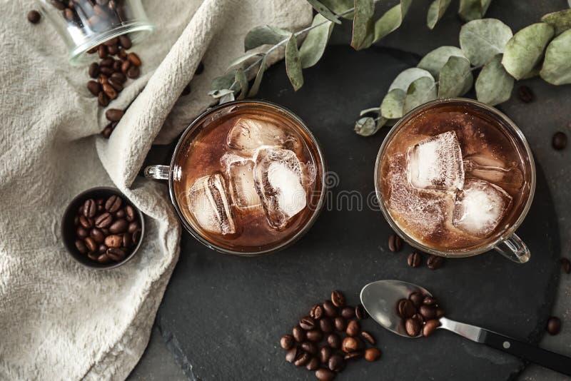 玻璃杯子用在板岩板材的冷的咖啡 图库摄影