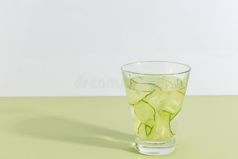 玻璃杯子用在浅绿色的背景的黄瓜水 Minimalistic创造性的概念 复制空间 库存图片