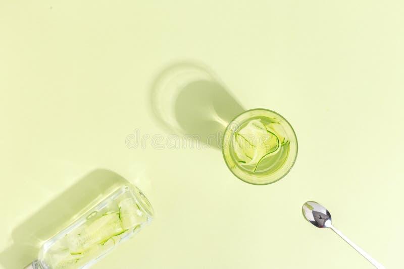 玻璃杯子用在浅绿色的背景的黄瓜水 Minimalistic创造性的概念 复制空间 免版税库存图片