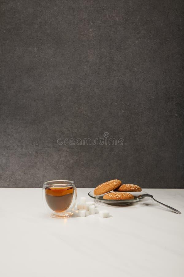 玻璃杯子用新鲜的热的茶和鲜美麦甜饼在灰色 图库摄影