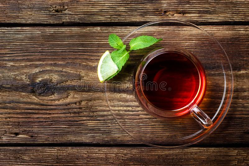 玻璃杯子用茶、薄菏和柠檬在木土气背景 免版税库存图片