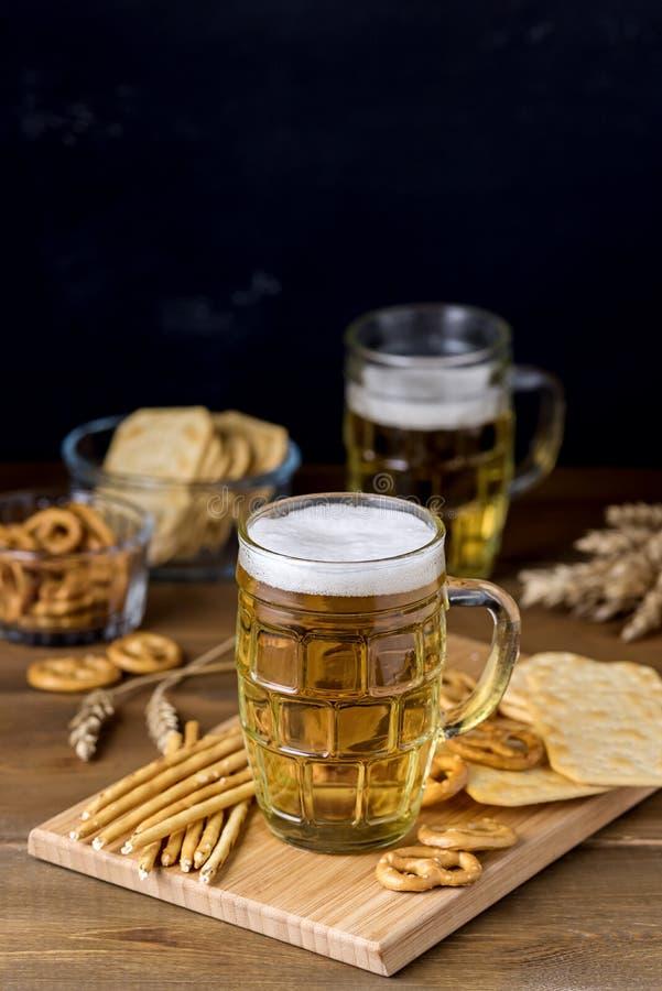 玻璃杯子鲜美低度黄啤酒和快餐在木表椒盐脆饼薄脆饼干与绍尔特垂直 免版税库存照片