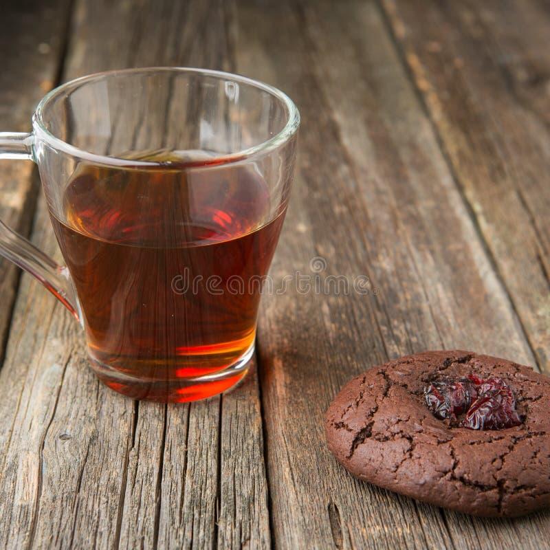 玻璃杯热的红茶和巧克力曲奇饼 库存照片