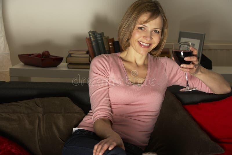 玻璃松弛电视注意的酒妇女 库存照片