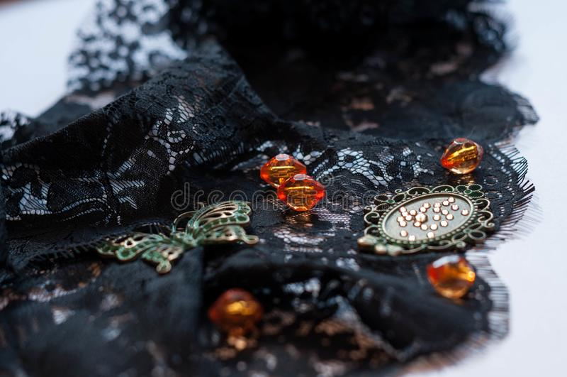 玻璃橙色小珠、绿色小框架与假钻石和装饰蝴蝶在黑鞋带 库存照片