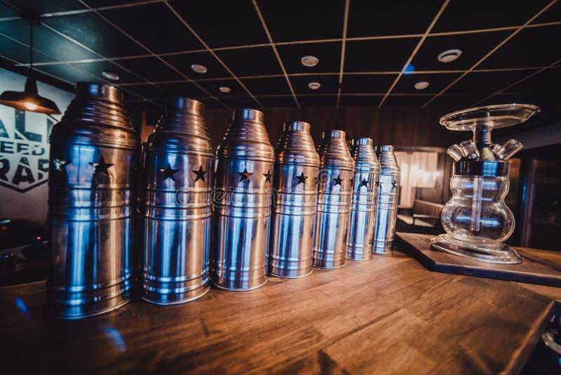 玻璃水烟筒在与许多水烟筒盖帽的一张木桌上站立 免版税库存图片