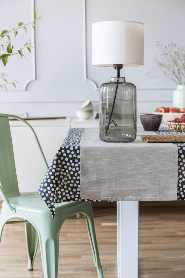 玻璃灯的特写镜头在一张桌的在每日室内部的一把绿色椅子旁边 实际照片 免版税库存图片