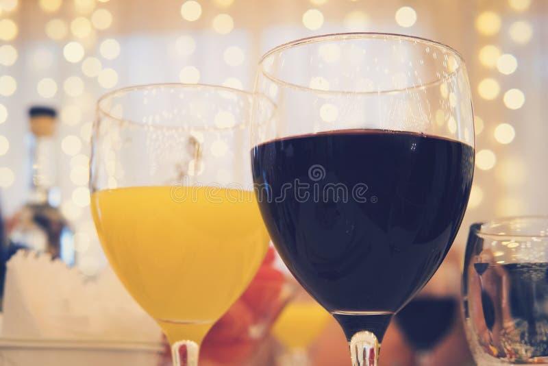 玻璃特写镜头视图用红葡萄酒和橙汁在一张桌上在餐馆诗歌选帷幕背景的 被填装的glasse 免版税库存图片