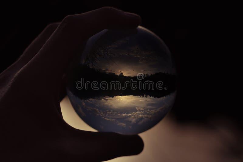 玻璃球在手中与日落反射 库存照片