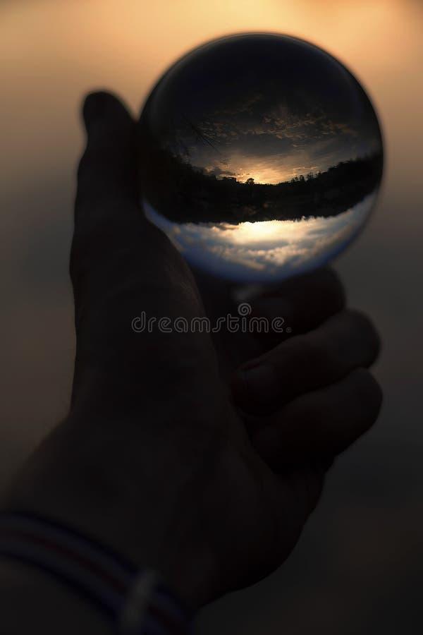 玻璃球在手中与日落反射 图库摄影