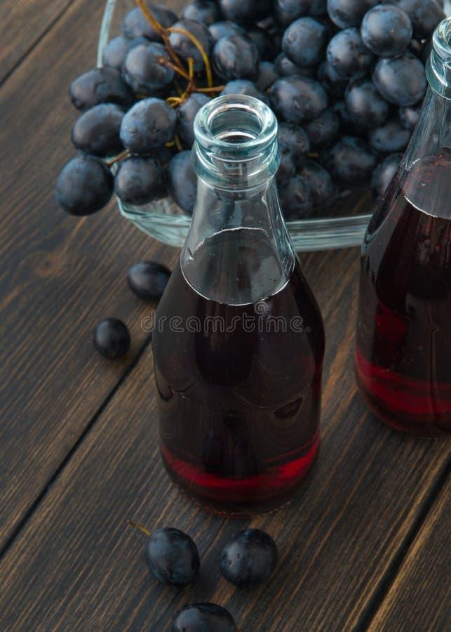 玻璃瓶与一束的新鲜的年轻红葡萄酒黑grap 库存图片