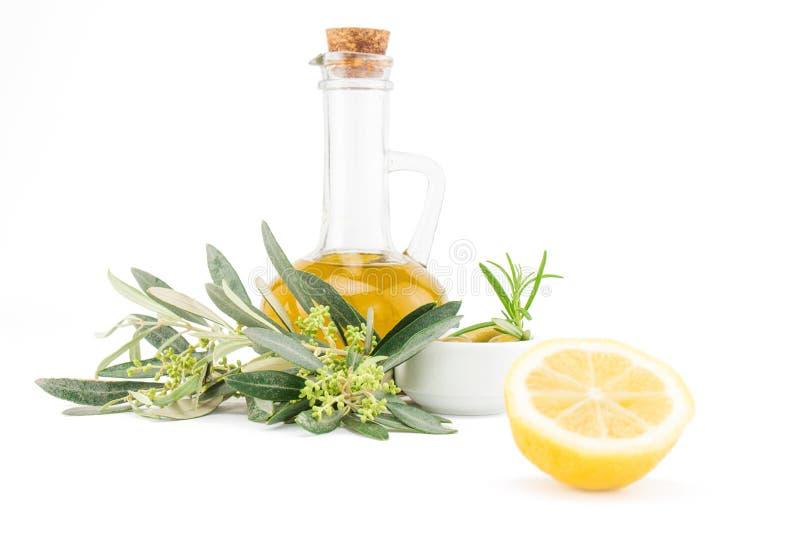 玻璃瓶优质处女橄榄油、柠檬和一些橄榄 图库摄影