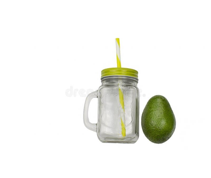 玻璃瓶子、在白色背景和秸杆隔绝的杯子有盖子的,把柄 透亮杯子和鲕梨 图库摄影