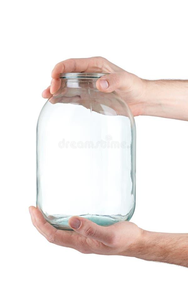 玻璃瓶子在手中在白色背景 免版税库存图片