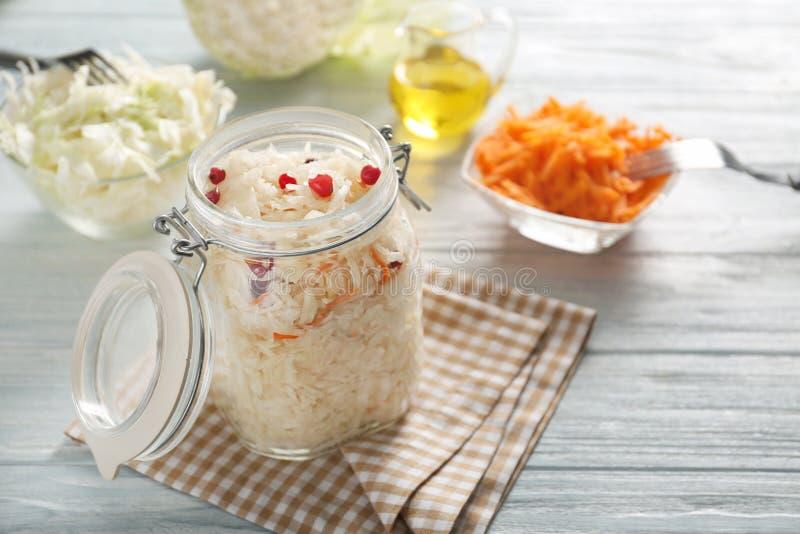 玻璃瓶子用可口德国泡菜和蔓越桔在木桌上 库存图片