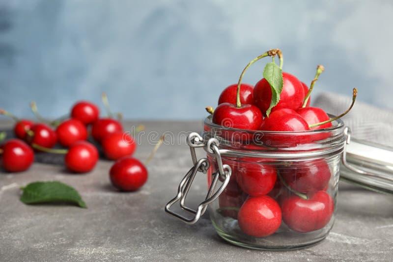 玻璃瓶子用在灰色桌上的成熟甜樱桃 库存照片