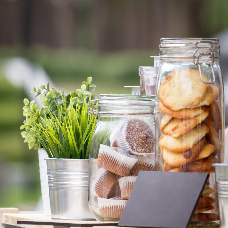 玻璃瓶子用曲奇饼和松饼,在金属装饰桶的绿色幼木 免版税图库摄影