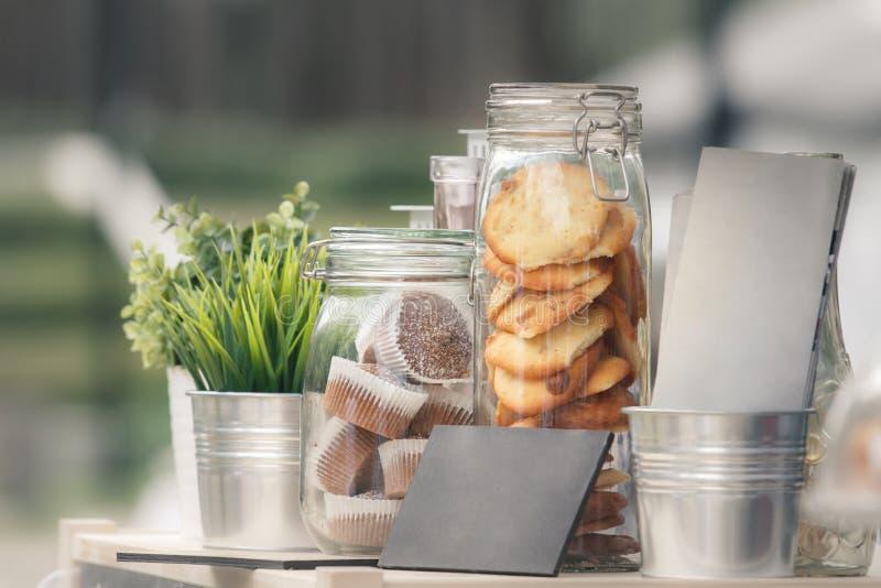 玻璃瓶子用曲奇饼和松饼,在金属装饰桶的绿色幼木 库存照片