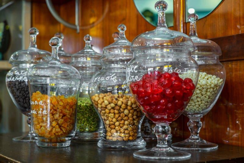 玻璃瓶子用糖煮的樱桃、咖啡豆、糖煮的桔子、榛子、开心果和白色巧克力 免版税库存照片