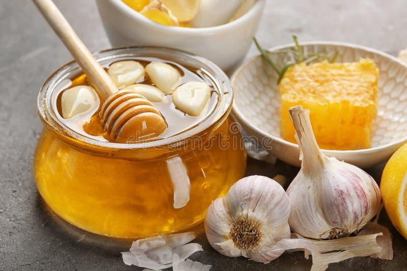 玻璃瓶子用蜂蜜和大蒜在桌上, 库存图片