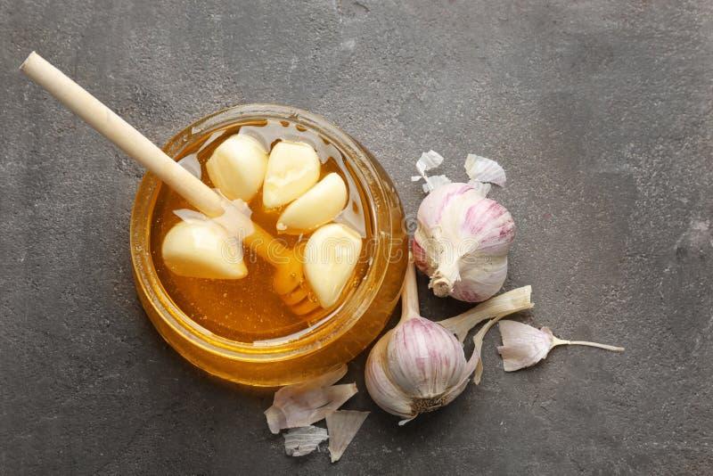 玻璃瓶子用蜂蜜和大蒜 库存图片