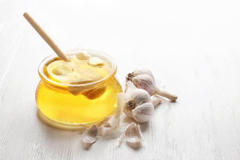 玻璃瓶子用蜂蜜和大蒜 免版税库存图片