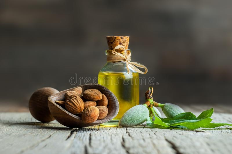 玻璃瓶扁桃仁油和杏仁坚果在木铁锹用绿色新鲜的未加工的杏仁在木桌上 图库摄影