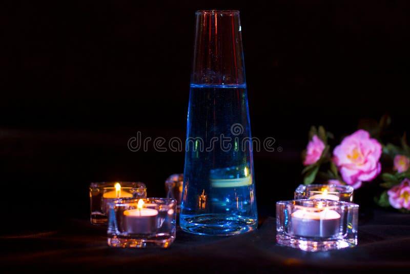 玻璃瓶用在黑暗的背景的蓝色魔药 免版税图库摄影