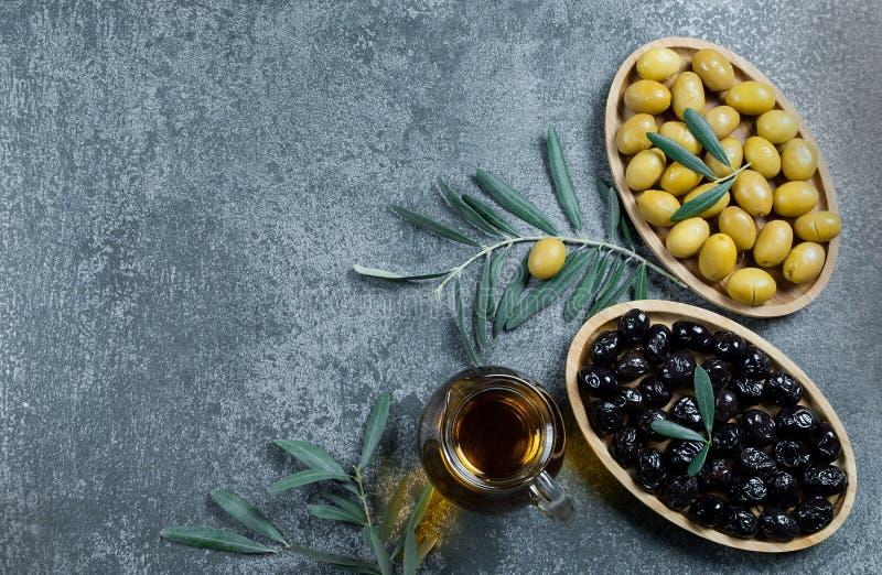 玻璃瓶自创橄榄油和橄榄树分支,未加工的土耳其绿色和黑橄榄种子和叶子在灰色土气桌上 图库摄影