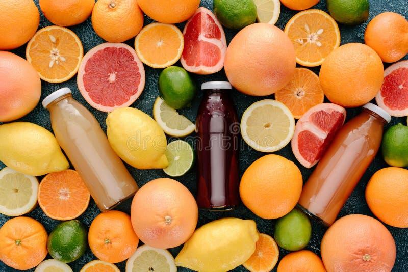 玻璃瓶顶视图新鲜的汁液围拢与在蓝色的柑橘水果切片 库存照片