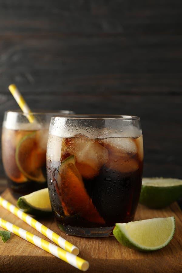 玻璃用冰可乐、石灰切片和小管 免版税库存图片