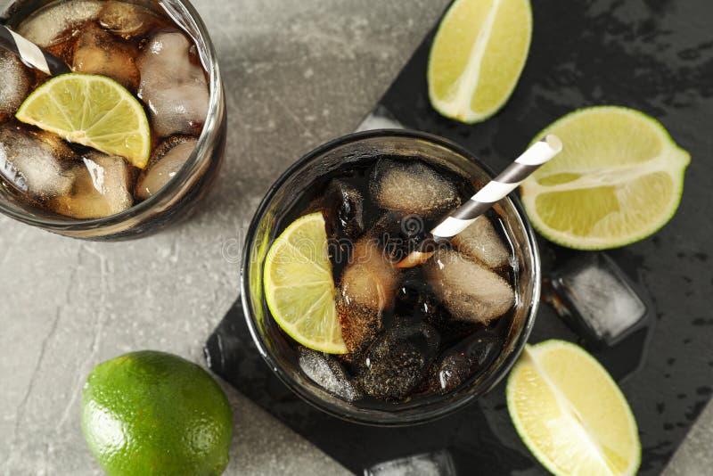 玻璃用冷的可乐和柑橘在灰色桌上 免版税库存图片