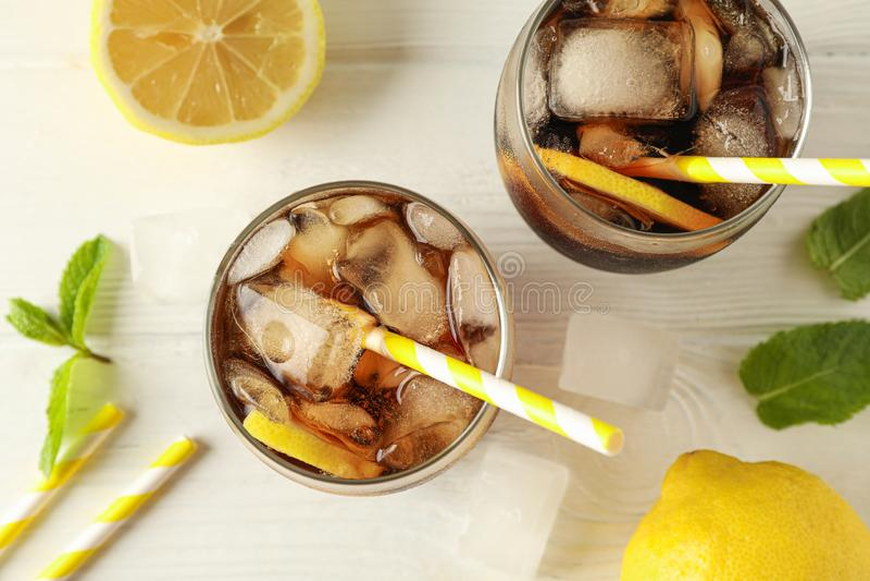 玻璃用冷的可乐和柑橘在白色木背景 库存图片