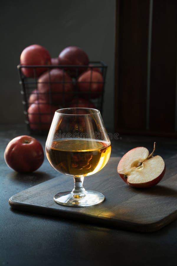 玻璃用卡尔瓦多斯白兰地酒和红色苹果在黑色 免版税库存照片