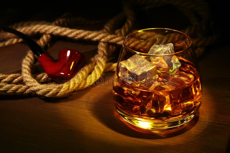 玻璃用威士忌酒、冰块和烟斗在木背景 免版税库存照片
