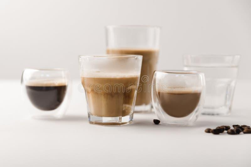 玻璃用被分类的咖啡在白色背景喝用咖啡豆 图库摄影