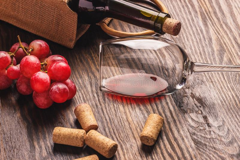 玻璃用酒、瓶和束成熟葡萄,木背景 免版税库存图片