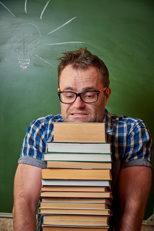 玻璃的一被弄乱的不剃须的年轻人拿着重的堆书 免版税库存图片