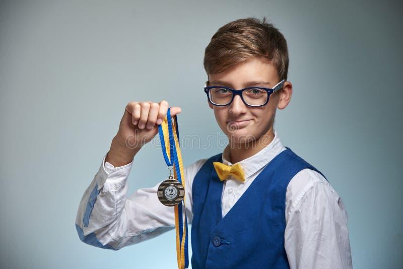 玻璃的与一枚银牌-学会的奖励男孩学生 免版税库存图片