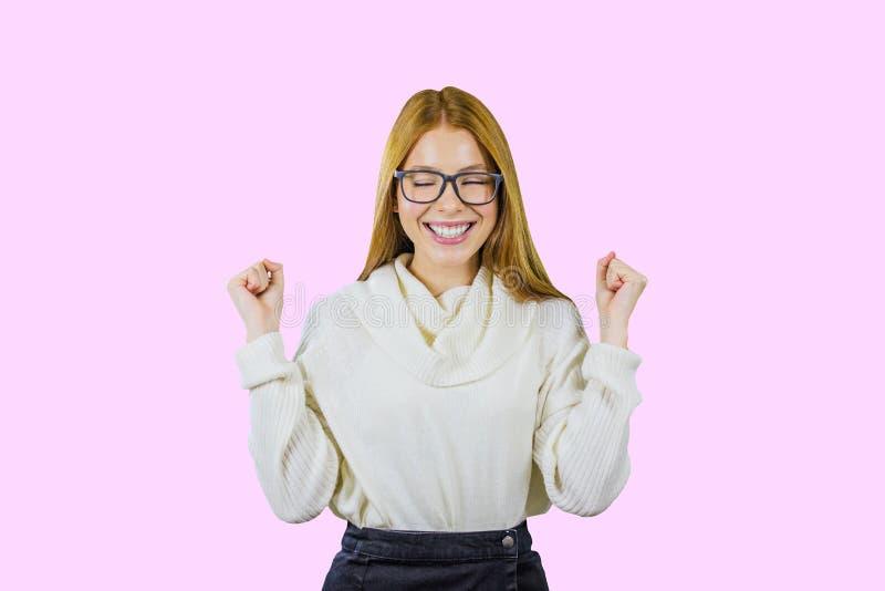 玻璃的和一件白色毛线衣的握紧她的拳头和举微笑,眼睛的红发女孩的画象关闭了 库存图片