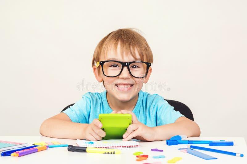 玻璃的天才男孩坐在书桌 在家做家庭作业的愉快的男孩 玻璃学习的逗人喜爱的聪明的男孩 回到学校 C 免版税库存照片
