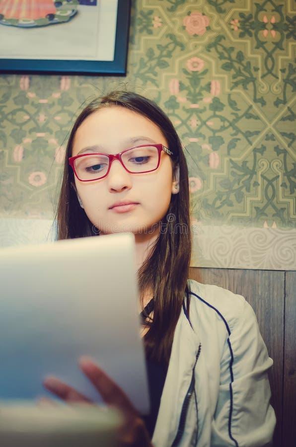 玻璃的女孩在咖啡馆在笔记本坐并且写 库存照片