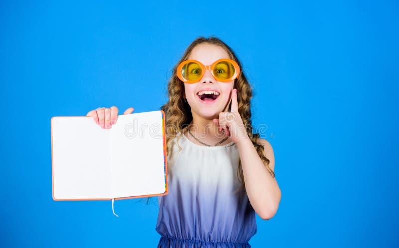 玻璃的小愉快的女孩与笔记本 做计划的夏天休假和假期 小秀丽女孩写她 免版税图库摄影