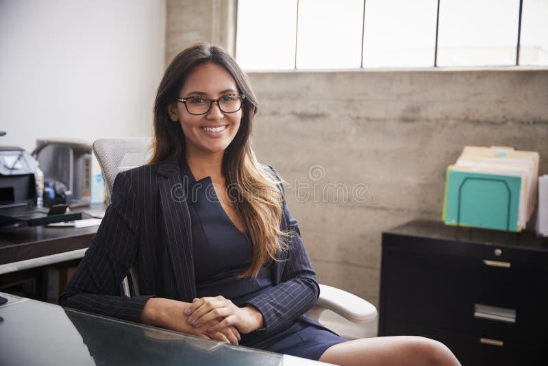 玻璃的少妇坐在办公桌微笑对照相机的 库存图片