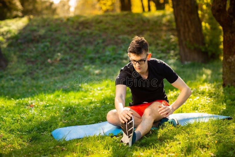 玻璃的年轻人训练瑜伽的户外 运动的人在一张蓝色瑜伽席子做放松的锻炼,在公园 r 库存图片