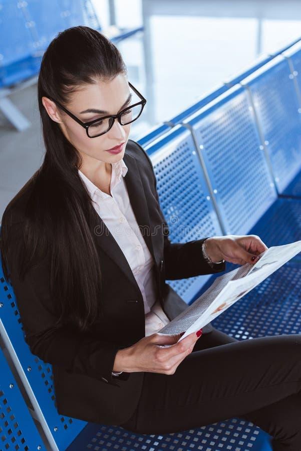 玻璃的年轻美丽的女实业家读报纸的在离开休息室 免版税库存图片
