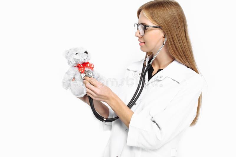 玻璃的年轻美丽的实习生医生,听t的女孩 免版税图库摄影