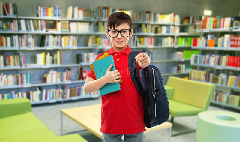 玻璃的微笑的男小学生与在图书馆的书 库存图片
