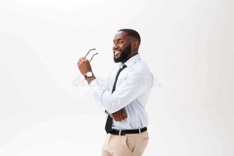 玻璃的微笑英俊的美国黑人的人,当在家时工作 免版税图库摄影